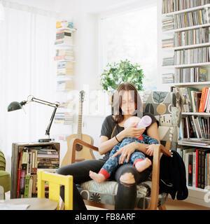 Schweden, Frau füttern ihr Baby (12-17 Monate) mit Flasche im Wohnraum - Stockfoto