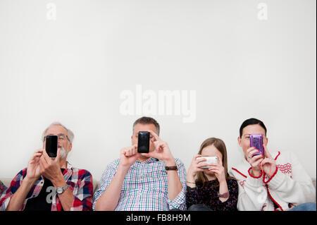 Mädchen (8-9) SMS mit Familie auf sofa - Stockfoto