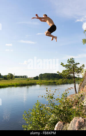 Schweden, Ostergotland, Mjolby, junger Mann in Svartan Fluss springen - Stockfoto