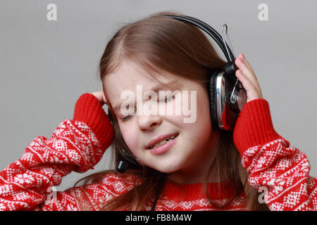 Schöne kaukasisches Mädchen tragen rote Christmas Sweater singen - Stockfoto