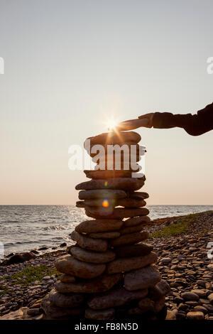 Schweden, Öland, Gronhogen, Boy (10-11), der letzte Stein auf Stein heap - Stockfoto