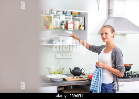 Junge Frau beim Abwasch in der modernen Küche mit Geschirrspüler, indem die Gerichte in ihren Platz - Stockfoto