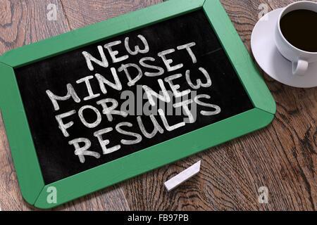 Neues Denken für neue Ergebnisse - grüne Tafel mit handgezeichneten Motivation Zitat und weißen Tasse Kaffee auf - Stockfoto