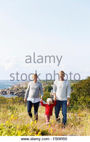Schweden, Stockholmer Schären, Sodermanland, Oja, Frau und Mann zu Fuß mit Sohn (2-3) durch Wiese mit Meer im Hintergrund - Stockfoto