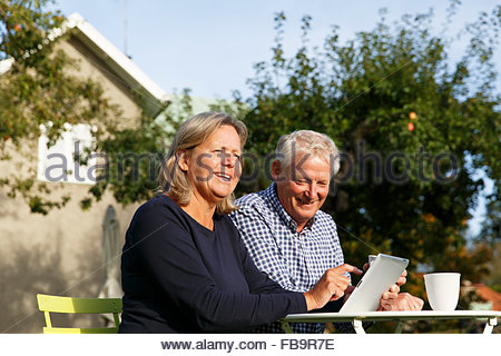 Schweden, Sodermanland, Senior paar tun Finanzplanung mit digital-Tablette am Tisch im Hinterhof - Stockfoto
