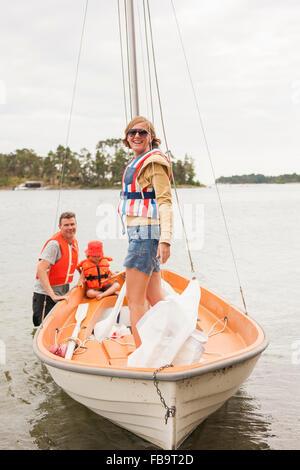 Schweden, Sodermanland, Stockholmer Schären, Musko, Familie mit Kind (4-5) tragen Schwimmwesten Segelboot am Fluss - Stockfoto
