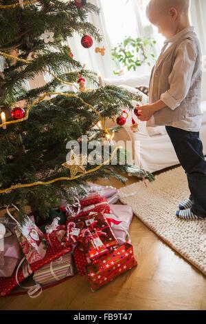 Schweden, kleine blonde junge (4-5) stehen neben Weihnachtsbaum