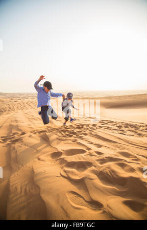Vereinigte Arabische Emirate, Dubai, zwei jungen (6-7, 8-9) springen auf Sand in der Wüste - Stockfoto