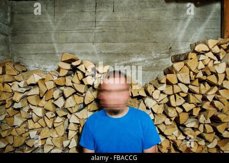 Finnland, Heinola, Mann mit verschwommenes Gesicht gegen Holzstoß Stockfoto
