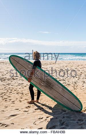 Australien, Queensland, Sunshine Coast, Noosa, Alexandria Bay, junge Mann Holding Surfbrett am Strand - Stockfoto