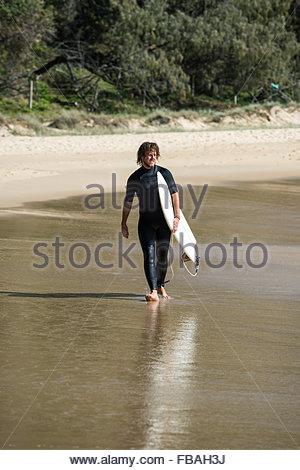 Australien, Queensland, Sunshine Coast, Noosa, Alexandria Bay, junger Mann mit Surfbrett am Strand - Stockfoto