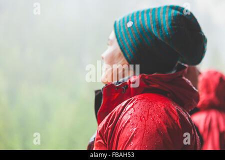Schweiz, Ausserferrera, junge Frau trägt warme rote Jacke und Wollmütze