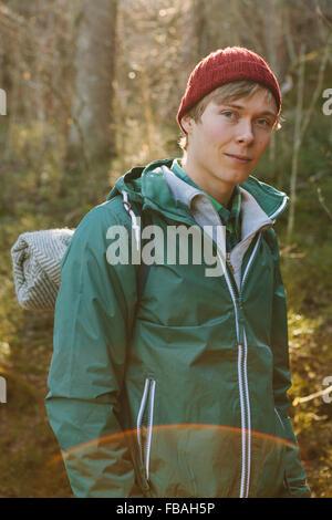 Finnland, ESO, Kvarntrask, Porträt des jungen Mannes mit wolligen Hut und Windjacke Jacke im Wald - Stockfoto