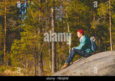 Finnland, ESO, Kvarntrask, junger Mann sitzt auf der Steinoberfläche im Wald - Stockfoto