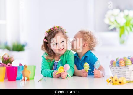 Kinder malen bunte Eiern. Kinder malen und dekorieren Osterei. Kleinkind Kind und Vorschüler Kind spielen drinnen - Stockfoto