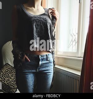 Mittelteil der Frau zu Hause Fenster stand - Stockfoto