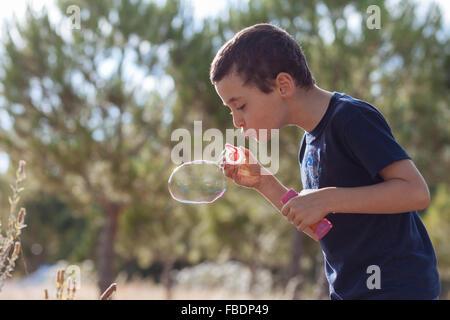 Boy bläst Seifenblasen auf Pflanzen - Stockfoto