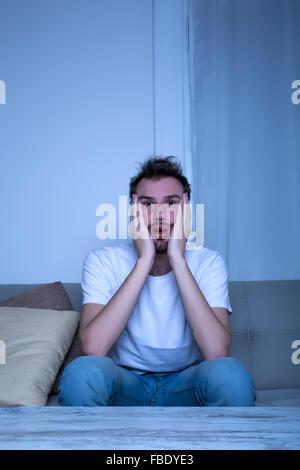 Ein junger Mann sitzt auf dem Sofa im Wohnzimmer ist schockiert über einen Film auf dem TV in der Nacht.