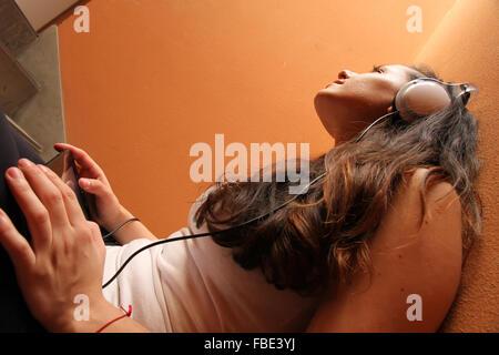 Eine junge Frau, die melancholische Musik sitzen im Treppenhaus. - Stockfoto