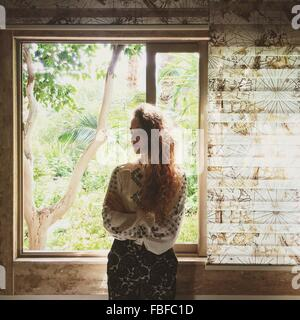Schöne junge Frau, die Fenster zu Hause stand - Stockfoto
