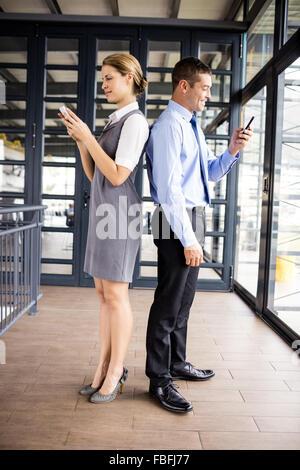 Geschäftsleuten stehen Rücken an Rücken mit Telefon - Stockfoto