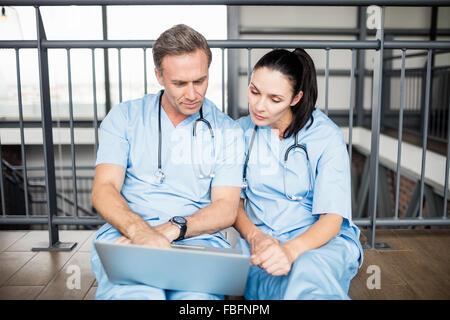 Ärzte mit Laptop sitzend auf Etage - Stockfoto