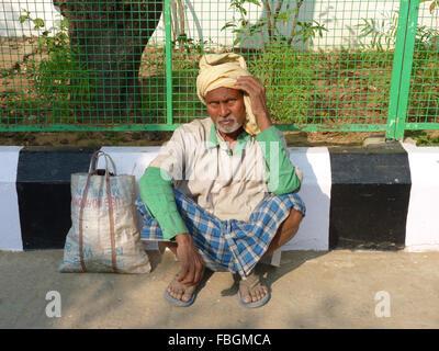 Ein armer indischer Mann auf der Straße sitzen - Stockfoto