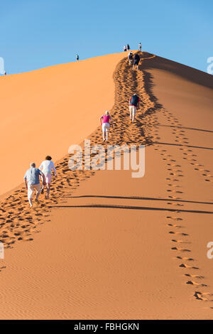 Touristen Klettern Sanddüne, Sossusvlei, Namib-Wüste, Namib-Naukluft-Park, Hardap Region Republik Namibia - Stockfoto
