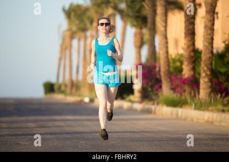 Fit junge Frau in Turnschuhen-Arbeit Joggen heraus auf den sonnigen Sommer Straße in Tropen, Palmen im Hintergrund - Stockfoto