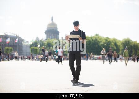 Junge hübsche Reisender Mann mit Rucksack tragen legere Kleidung und Mütze Blick auf Karte, auf der Suche nach Richtung - Stockfoto