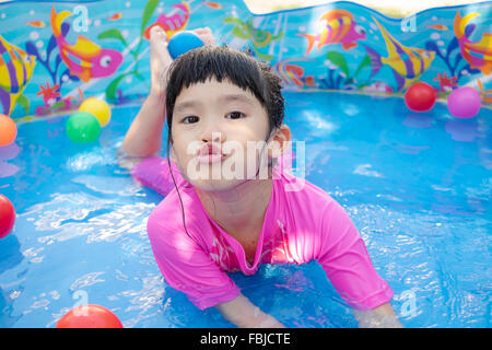 Ein kleines Mädchen in rosa Anzug spielt Wasser und Kugeln in blau Planschbecken - Stockfoto