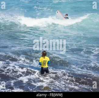 Weibliche Surflehrer stehen im Meer, die Lektion zu geben - Stockfoto