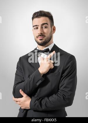 Secret Service-Agent oder Leibwächter imitieren Pistole mit Handzeichen Pistole Geste. Entsättigt Porträt über graue - Stockfoto