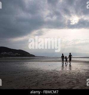 Silhouette von drei Kindern an Hand laufen am Strand - Stockfoto