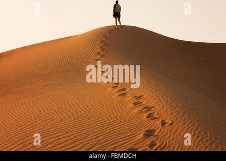 Frau stehend auf einer Sanddüne in der Wüste, Dubai, Vereinigte Arabische Emirate - Stockfoto