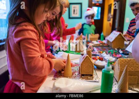 Kinder Lebkuchenhäuschen mit Süßigkeiten und Zuckerguss verzieren - Stockfoto