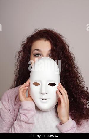 junge Frau, die Maske abnehmen - Stockfoto
