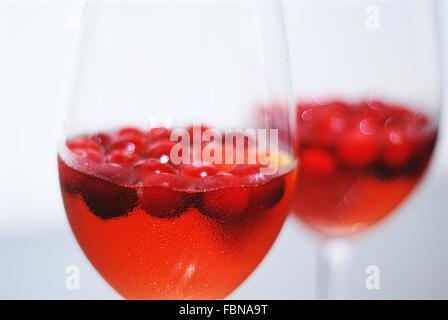 Zwei Gläser mit gekühlten Cocktail und frische Cranberries oder Cranberry Saft und Frische Cranberries. Ein Glas im Fokus ist.