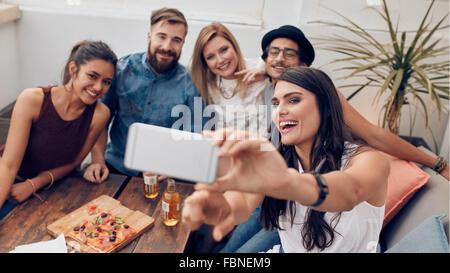 Gruppe von Freunden nehmen Selfie auf einem Smartphone. Junger Mann und Frauen, die ein Selbstporträt auf Handy. - Stockfoto