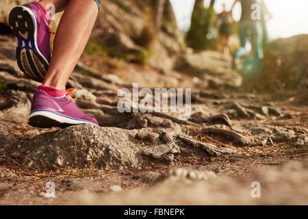 Ein Athlet der Füße tragen Sportschuhe auf einem anspruchsvollen Feldweg hautnah. Trail running Training auf felsigem - Stockfoto