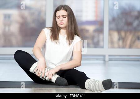 Porträt des verletzten unglücklich Fit junge schöne Frau im Sportverein, berühren den Knöchel nach dem Training - Stockfoto