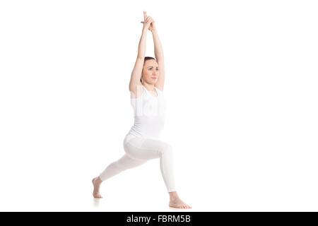 Sportlich schöne junge Frau in weißen Sportbekleidung Krieger ich Haltung, hohe Longe Übung Virabhadrasana 1 mit - Stockfoto