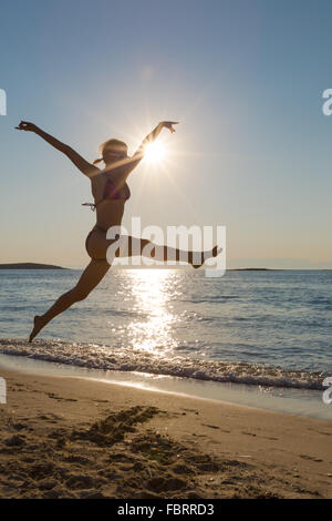 Frau springen Hintergrundbeleuchtung am Meeresstrand - Stockfoto