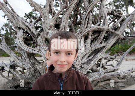Junge vor großen Stück Treibholz, Porträt - Stockfoto