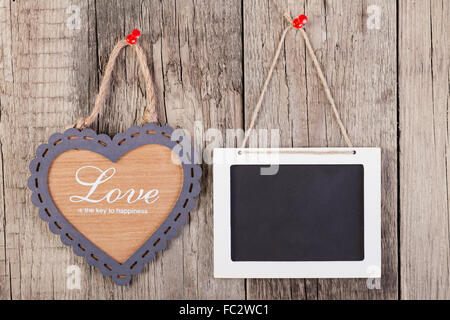 Leere hölzerne Tafel Zeichen und Herz Formrahmen mit Liebe Text auf hölzernen Hintergrund. - Stockfoto