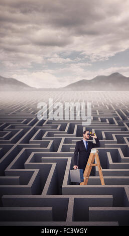 Zusammengesetztes Bild der Unternehmer auf der Suche auf einer Leiter - Stockfoto