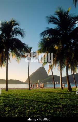 Menschen nehmen morgens joggen und spazieren Flamengo Beach in der Nähe von Sugar Loaf bei Sonnenaufgang in Rio - Stockfoto