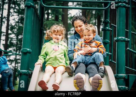 Kaukasische Mutter und Kinder spielen am Spielplatz