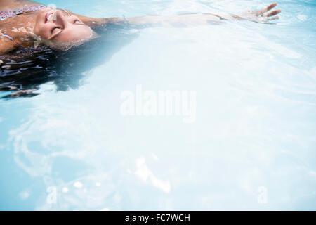 Kaukasische Frau schweben im Schwimmbad - Stockfoto