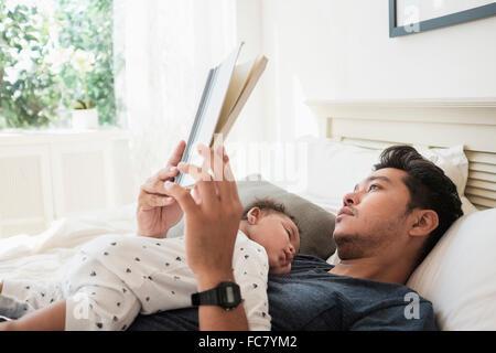 Vater mit schlafenden Baby Sohn lesen - Stockfoto
